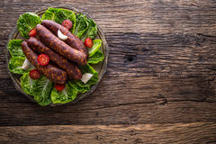 Sausages. Smoked Sausages. Chorizo sausages with vegetable rosemary spices and kitchen utensil Royalty Free Stock Photography