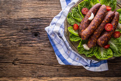 Sausages. Smoked Sausages. Chorizo sausages with vegetable rosemary spices and kitchen utensil Stock Image