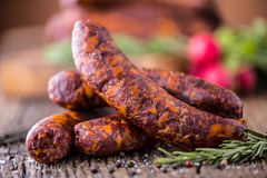 Sausages. Smoked Sausages. Chorizo sausages with vegetable rosemary spices and kitchen utensil Royalty Free Stock Photos