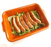 Sausages. Some fresh grilled sausages on salad Stock Photos
