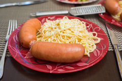 Sausages and spaghetti served with grinded white cheese Royalty Free Stock Photography
