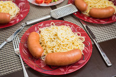 Sausages and spaghetti served with grinded white cheese Royalty Free Stock Photo