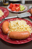 Sausages and spaghetti served with grinded white cheese Royalty Free Stock Photos