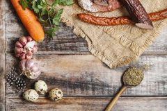 Sausages, spices and garlic on wooden table Royalty Free Stock Photo