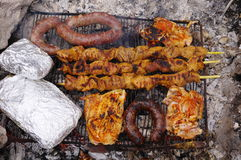 Sausages, steak and pork spit cooking on a grill Stock Photo