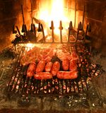 Sausages and steak in the grill of the fireplace. Sausages and meat cooking in the grill of the fireplace stock photography