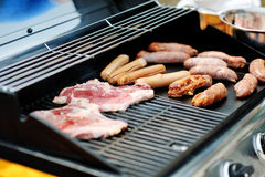 Sausages and steaks cooking on a barbecue grill. Delicious and tasty sausages and steaks cooking on a barbecue grill Royalty Free Stock Photos