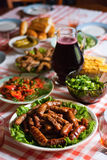 Sausages on the table. Grilled sausages on the table with salads Royalty Free Stock Photos