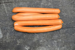 Sausages. Thin long suckers lie on a wooden surface Royalty Free Stock Photo