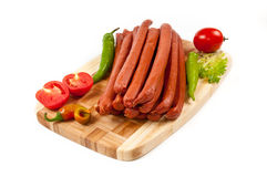 Sausages with a tomato and pepper on cutting board Stock Images