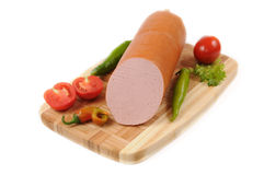 Sausages with a tomato and pepper on cutting board Royalty Free Stock Photography