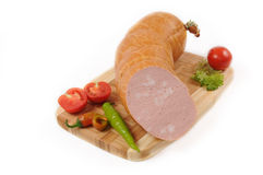 Sausages with a tomato and pepper on cutting board. Isolated on white Stock Photo