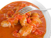 Sausages in tomato sauce with fork. Royalty Free Stock Image