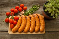 Sausages with tomatoes on a tray with spices Royalty Free Stock Photos