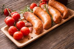 Sausages with tomatoes on a tray with spices Royalty Free Stock Images