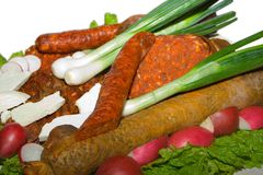 Sausages and vegetables Stock Photos