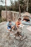 Couple of backpackers grilling some sausages and vegetables for picnic. Sausages and vegetables. Couple of young and active backpackers grilling some sausages royalty free stock photos