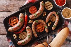 Sausages with vegetables on a grill closeup. horizontal top view Royalty Free Stock Image
