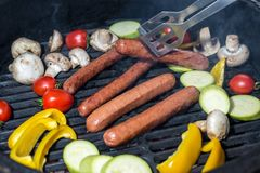 Sausages and vegetables on the grill stock images