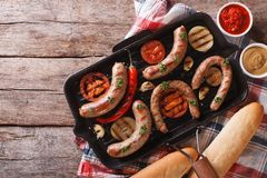 Sausages with vegetables in a pan grill. horizontal top view Royalty Free Stock Images