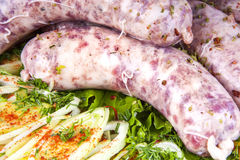 Sausages with vegetables. Raw sausages with vegetables and spices Stock Photography