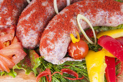Sausages with vegetables and spices. Raw sausages with vegetables and spices Royalty Free Stock Photos