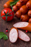 Sausages on wooden board. With cherry tomato Stock Photo