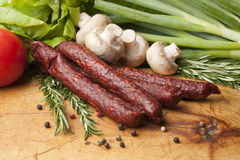 Sausages on a wooden board, close up. Wooden cutting board with sausages, peppercorns and rosemary Stock Photos