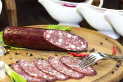 Sausages. On a wooden plate with vegetables in a restaurant stock image