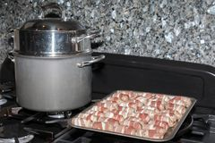 Sausages wraped in bacon. Laid on tray ready to be baked for Christmas dinner in the oven next to a saucepan on the top of a stove stock image