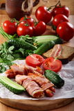Sausages wrapped in bacon with vegetables. Royalty Free Stock Image