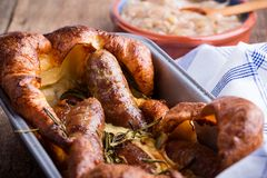 Sausages in Yorkshire pudding batter. Baked sausages in Yorkshire pudding batter and served with onion gravy, toad in the hole royalty free stock images
