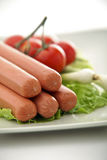 Sausages3. Cooked sausages served with tomato,  onions and salad and mustard Stock Images