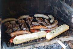 Saussages und Fleisch auf Grill Stockfotos