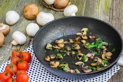 Sautéed plocka svamp den bruna och vita champignonen med persilja på PA Royaltyfri Fotografi