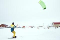 Saut à skis extrême de style libre avec le jeune homme à la saison d'hiver snowkiting Photos stock