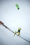 Saut à skis extrême de style libre avec le jeune homme à la saison d'hiver snowkiting Image libre de droits