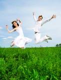 Saut de couples dans un pré Photo libre de droits