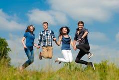 Saut heureux : groupe des jeunes à l'extérieur images libres de droits