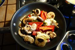Sautéing mushrooms and peppers Royalty Free Stock Photography