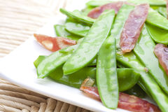 Sauted sausage and snow peas Stock Images