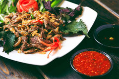 Sauteed beef with herbs and chili sauce on table Stock Photography