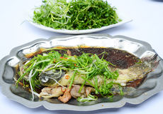 Sauteed grouper fish with soyal sauce, onion and vegetables on i Royalty Free Stock Images