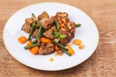 Sauteed lever med grönsaker på den vita plattan royaltyfri fotografi