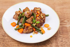 Sauteed liver with vegetables on white plate. View from above, top studio shot Royalty Free Stock Photography