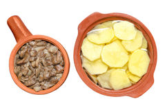 Sauteed mushrooms and raw sliced potatoes isolated on white background Royalty Free Stock Image