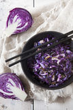 Sauteed purple cabbage on black bowl with japanese chopsticks on white wooden table Royalty Free Stock Photography