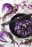 Sauteed purple cabbage on black bowl with japanese chopsticks on white wooden table Stock Photo