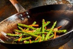 Sauteedmengeling van verse aspergespruiten en wortelen Stock Foto's