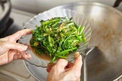 Sauteing японский шпинат Стоковое фото RF